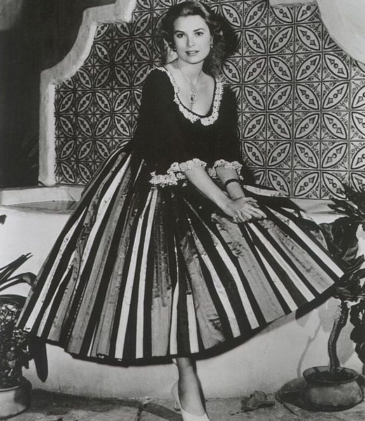 Грейс Келли в платье с пышной юбкой сидит на диванчике